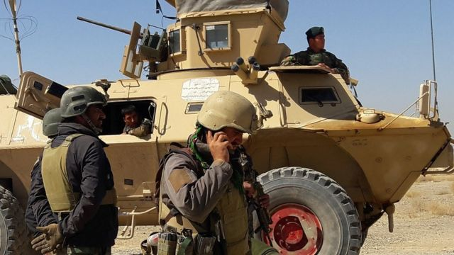Afghan security forces stand near an armoured vehicle during ongoing fighting between Afghan security forces and Taliban fighters in the Busharan area on the outskirts of Lashkar Gah, the capital city of Helmand province May 5, 2021.