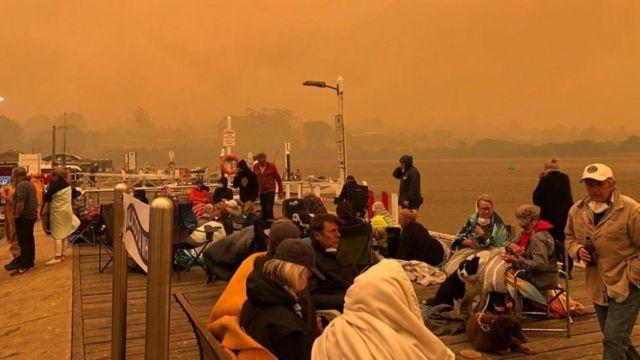 Gente a la espera en el embarcadero mientras el cielo se vuelve anaranjado