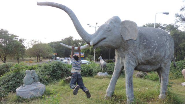 Un niño colgado de la estatua de un elefante en las afueras del zoológico de Islamabad.