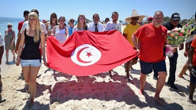 Tourists carry Tunisian flag after terror attack