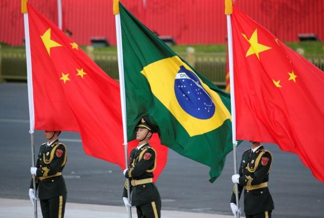 Guardas chineses seguram bandeiras do Brasil e da China