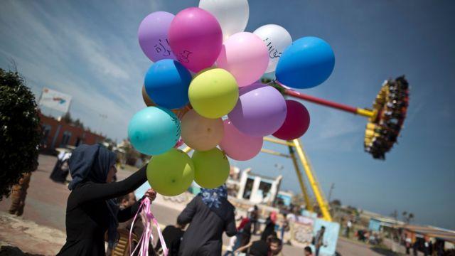 """امرأة في غزة تحمل بالونات كُتب عليها """"حق المرأة""""، في الثامن من مارس/آذار 2016"""
