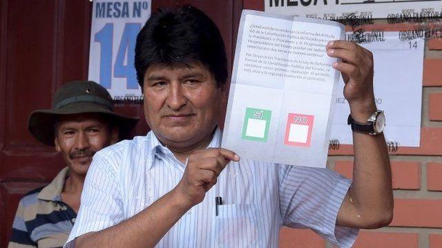 Bolivia's President Evo Morales holds a ballot paper