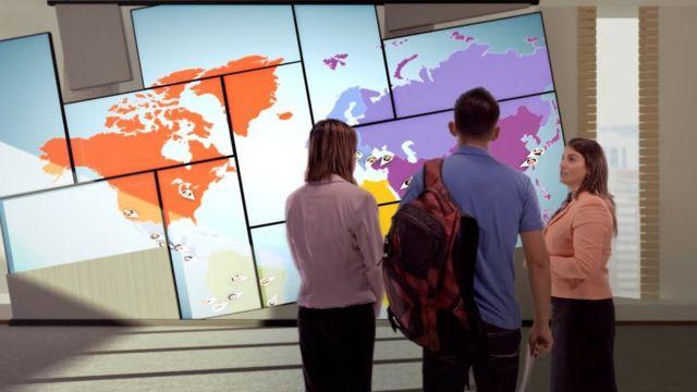 Una trabajadora de Laureate le muestra un mapa mundi a unos alumnos
