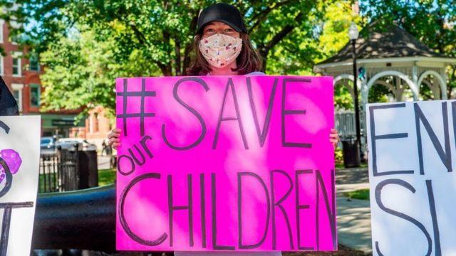Mulher adepta do QAnon exibe cartaz em que se lê: salvem nossas crianças