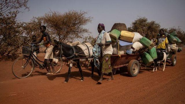 Des gens avec leurs affaires empilées sur une remorque de fortune tirée par un âne