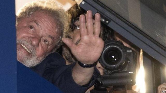 Forrmer Brazilian president Luis Inácio Lula da Silva waves to supporters from a window