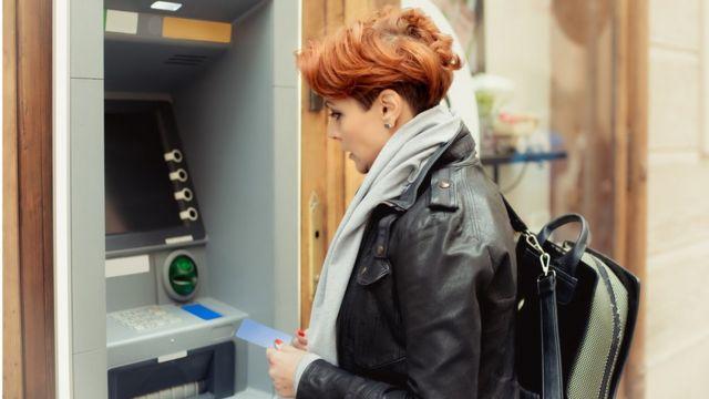 Mujer sacando dinero en un cajero