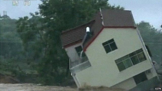 A house in China's Hubei province topples sideways as it collapses into floodwaters