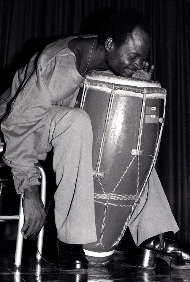 Un percusionista aprieta el mentón contra el cuero de un tambor