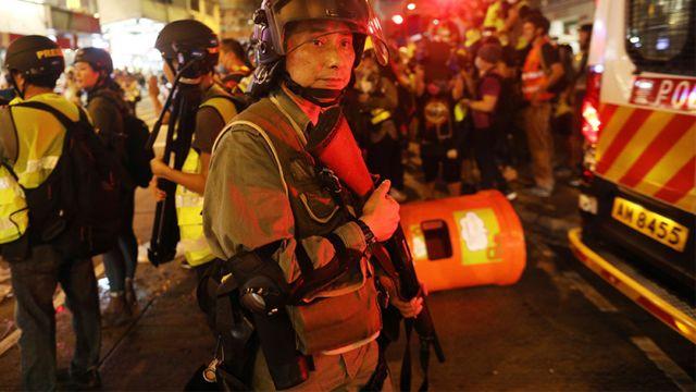 香港九龍旺角一名手持長槍防暴警員在被投擲垃圾桶的警車旁戒備(17/8/2019)