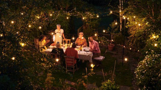 Sıcak bir yaz akşamı dışarıda konuşan ve yemek yiyen arkadaşlar