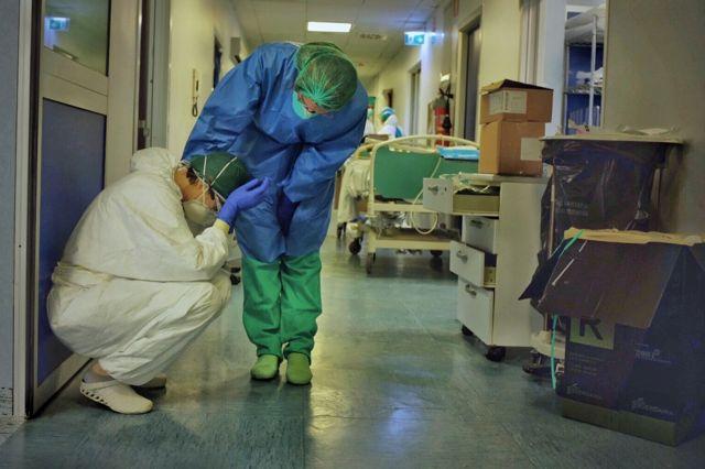 Em corredor de hospital, um membro da equipe consola outro, ajoelhado com as mãos na cabeça