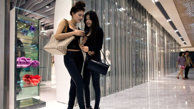Vietnamese fashion model Van Doll (L) hangs out with a fellow model in a new shopping mall February 24, 2011 in Ho Chi Minh City, Vietnam