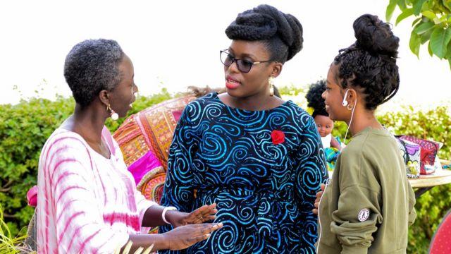 Liliane Coulibaly, propriétaire d'un salon de coiffure pour cheveux naturels (au centre) discutant avec une femme et une jeune fille lors du Dakar Hair Day.