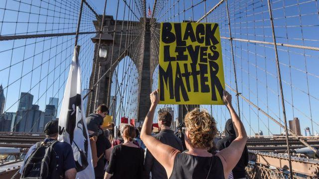 Manifestante com cartaz do Black Lives Matter em passeata em Nova York