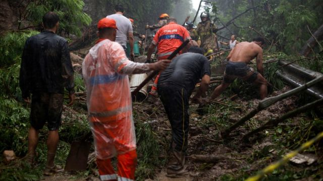Firefighters and volunteers take part in a rescue operation after a mudslide