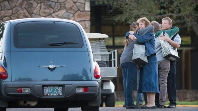 Staff members embrace as they return to work at Umpqua Community College