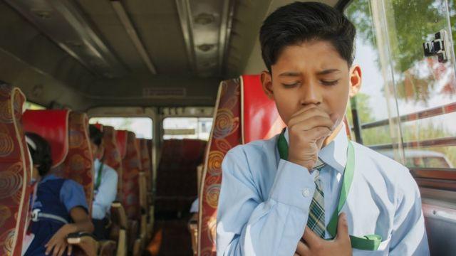 Niño tosiendo en un bus.