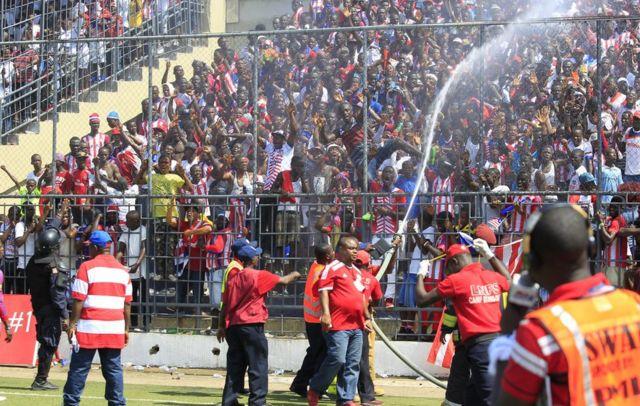 Abajejw ekuzimya umuriro bateye amazi abafana imbere y' ureukino rwagoma guhuza Liberia na Togo ku kibuga c' iMonromvia ca Antoinette Tubman Stadium, 05/06/2016.