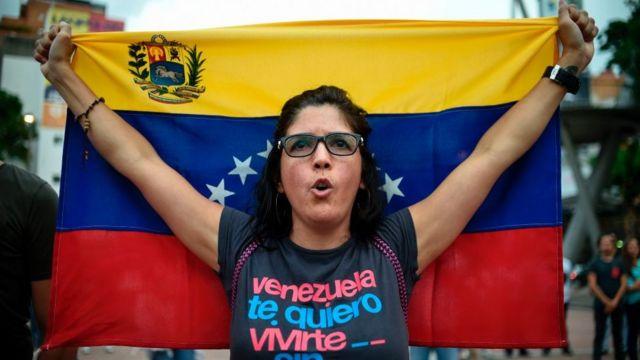 Una mujer con una bandera de Venezuela.