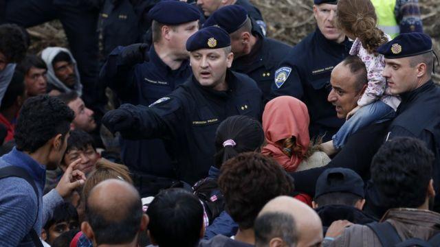 セルビアとの国境で移民に指示するクロアチア警官(18日)