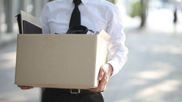 Homem engravatado segura uma caixa com seus materiais de escritório após ser demitido