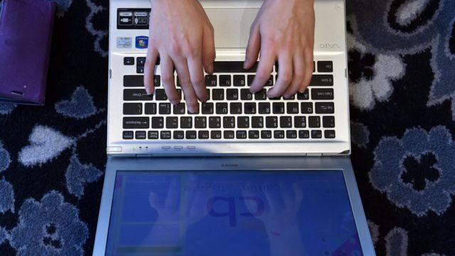 Manos sobre un teclado de computadora portátil.