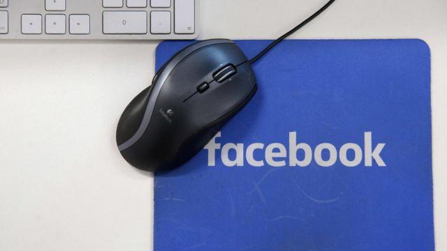 Mouse e teclado próximos a mousepad com marca do Facebook