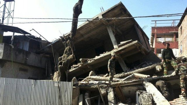Soldiers inspect a collapsed property in Imphal