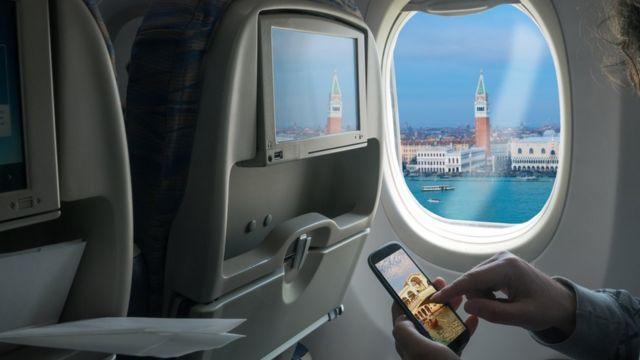 Чоловік користується мобільним в літаку