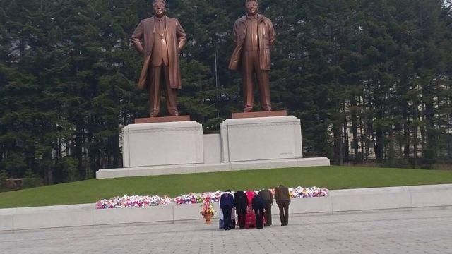 કોરિયામ લીડરોના સ્ટેચ્યુ સામે આદાર આપતા કોરિયન લોકોની તસવીર