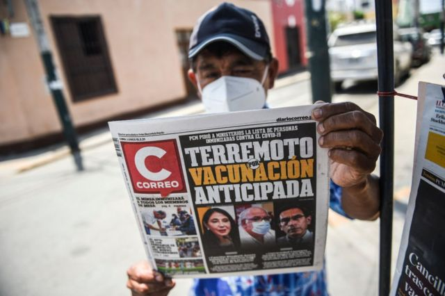 Man holds a newspaper that dedicates the cover to the scandal.