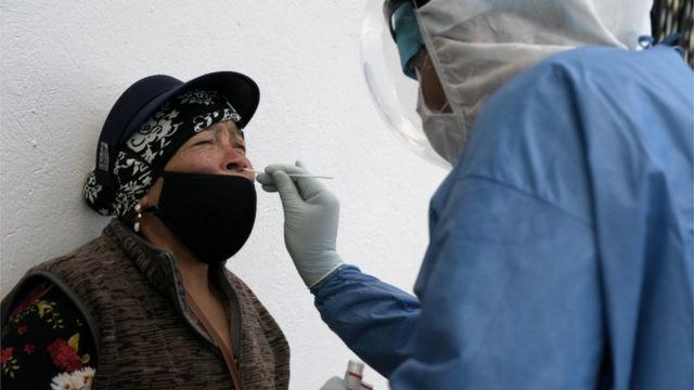 Profissional de saúde coleta amostra do nariz de uma mulher equatoriana para exame de covid-19