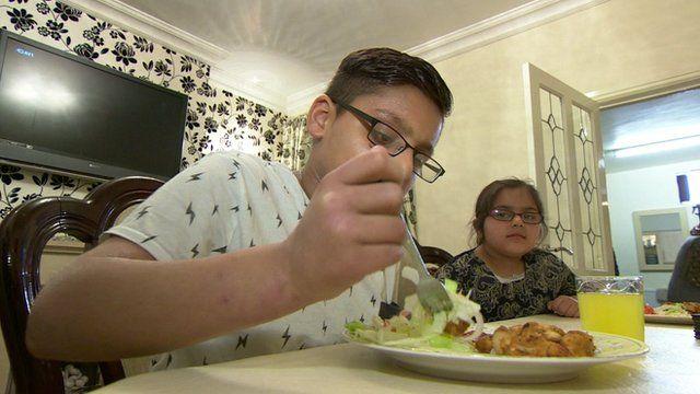 Sahil (l) eating his dinner