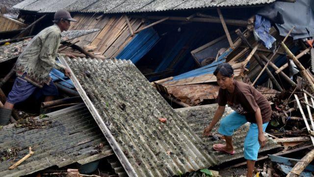 Warga yang rumahnya roboh dihantam tsunami mengambil atap untuk dipasang lagi di Kampung Sinar Laut, Kecamatan Panimbang, Pandeglang, Banten, Minggu (23/12)