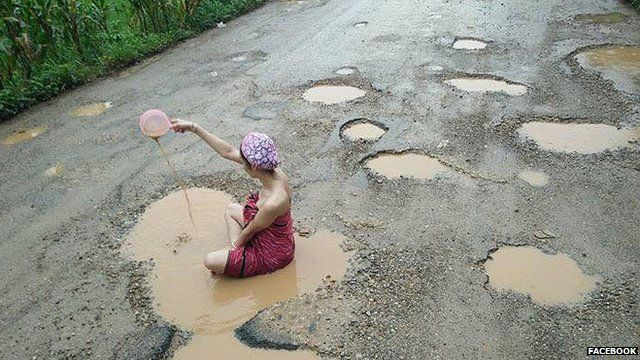 Woman bathing in a pothole in Thailand