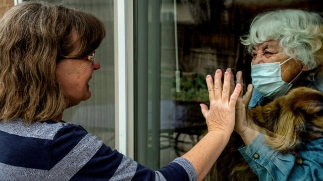 Madre e hija se dan la mano con una ventana de vidrio de por medio