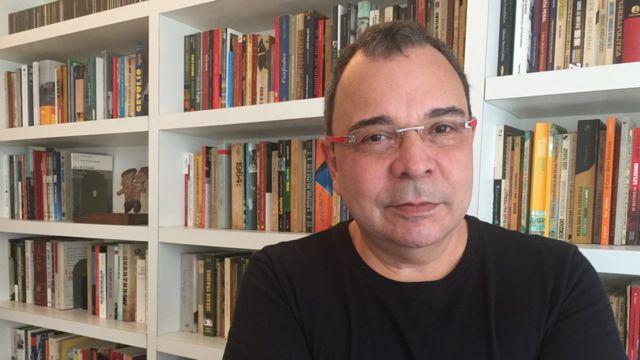 Fotografia de Carlos Fico em frente a uma estante de livros