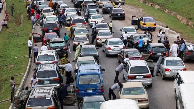 People wait next to their cars on the Abuja - Nasarawa road due to clashes between Nigerian soldiers and members of Islamic Movement of Nigeria