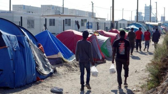"Migrants walk in the northern area of the camp called the ""Jungle"" in Calais,"