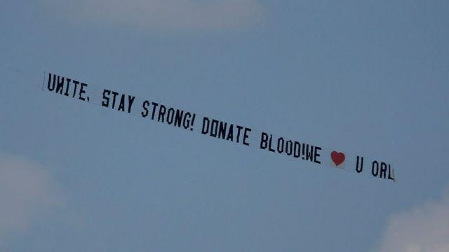 """Valla aérea remolcada por una avioneta lee: """"Unidos somos fuertes, dona sangre""""."""