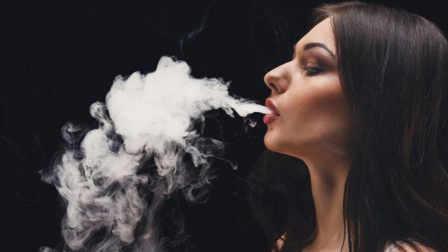 Mujer sacando humo por la boca.