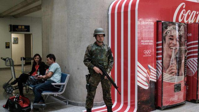 Un soldado en guardia al lado de una publicidad de Coca Cola