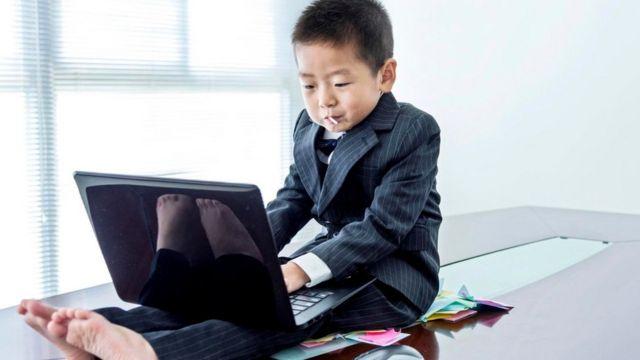 Un niño vestido de ejecutivo con una laptop