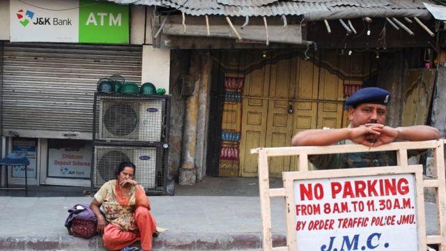 ज्म्मू में पैसे के लिए एक एटीएम के बाहर बैठी महिला.
