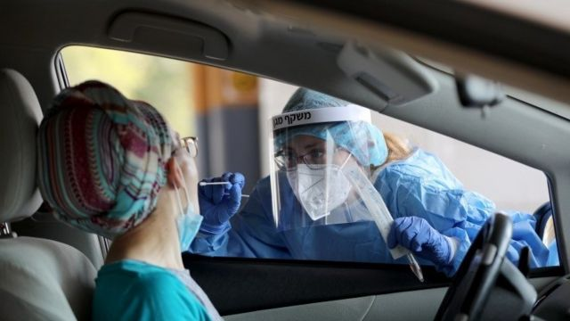 A member of the Shaare Zedek Hospital Medical team issues a coronavirus examination outside the biological emergency room that treats coronavirus patients at Shaare Zedek Hospital in Jerusalem, Israel, 11 September 2020.