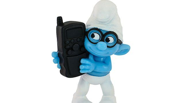 Smurf toy holding mobile phone