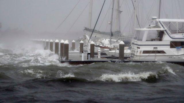 Un puerto con varios barcos golpeado por las olas.