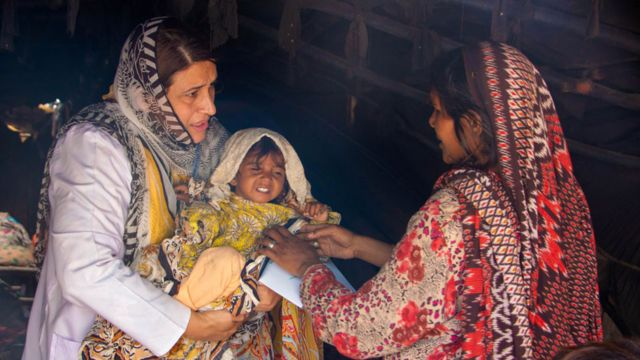 Dr Uzma Khan with a mother and child